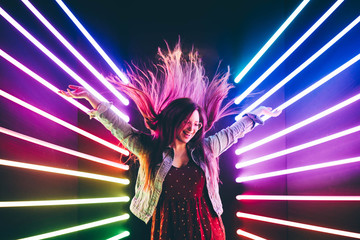 Papiers peints Magasin de musique Attractive dancing girl, hair flying, neon light. Portrait of girl posing with hands up.