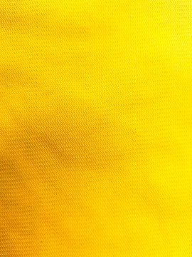 Texture background of yellow cotton fabric with wrinkles.