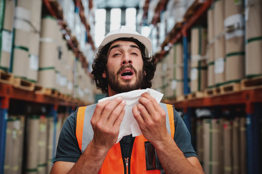 Young caucasian warehouse supervisor sneezing while feeling sick of cold