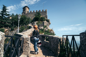 Woman posing. Dressed in a motorcycle outfit and sunglasses. body protection turtle and knee pads, helmet in hand. Fortress, stone steps, stairs. Journey, vacation. Pass of the witches San Marino Wall mural