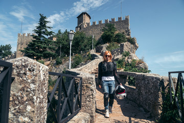 Woman hiking. dressed in a motorcycle outfit and sunglasses. body protection turtle and knee pads, helmet in hand. Fortress, stone steps, stairs. Journey, vacation. Pass of the witches San Marino Wall mural