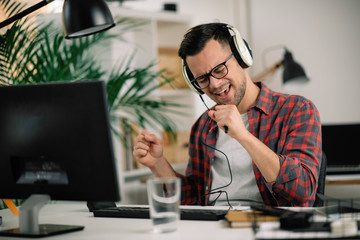 Attractive businessman in office. Young programmer with headphones singing at work. Fotobehang