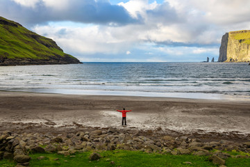 Tourist standing at the beach in Tjornuvik in the Faroe Islands, Denmark