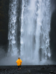 Tourist wearing a yellow raincoat walks to the Skogafoss waterfall in Iceland