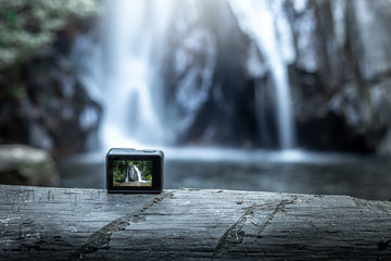 action camera on wood with the waterfall behind.