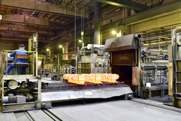 hardening of steel components in a foundry - red-hot components come out of the oven