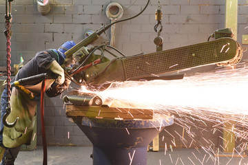 Workers in protective equipment in a foundry work on a casting with a grinding machine at the workplace