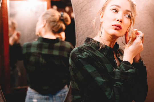 Young woman putting on hoop earring while standing in front of mirror at home getting ready to go out