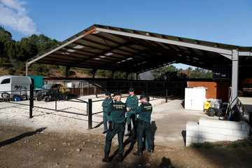 Spanish civil guards stand outside an illegal underground tobacco factory during a police raid in Monda