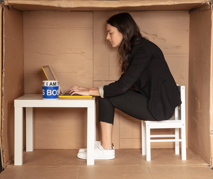 young beautiful businesswoman sitting in office cardboard box, focused working on computer