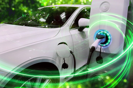 EV Car or Electric vehicle at charging station with the power cable supply plugged in on blurred nature with green energy power effect. Eco-friendly sustainable energy concept.