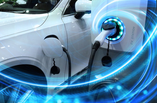 EV Car or Electric vehicle at charging station with the power cable supply plugged in on blurred nature with blue energy power effect. Eco-friendly sustainable energy concept.