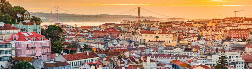 Spoed Fotobehang Oude gebouw A view of the Alfama downtown and the 25 April Bridge.