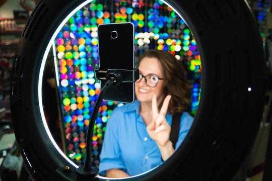 Woman uses LED lamp with a phone for selfie