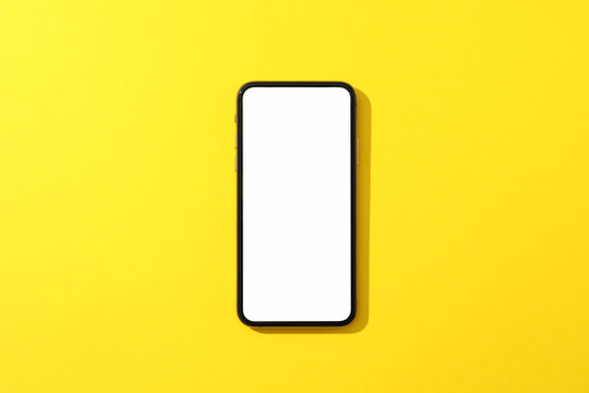 Phone with empty screen on yellow background, top view