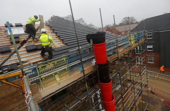 Builders work on the roof of a building at a Barratt housing development near Haywards Heath