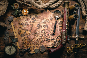 Pirate treasure map and human skull on brown wooden table closeup background.