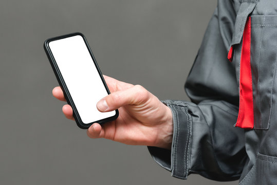 A blank screen mobile phone with copy space in plumber or auto mechanic hand close up.
