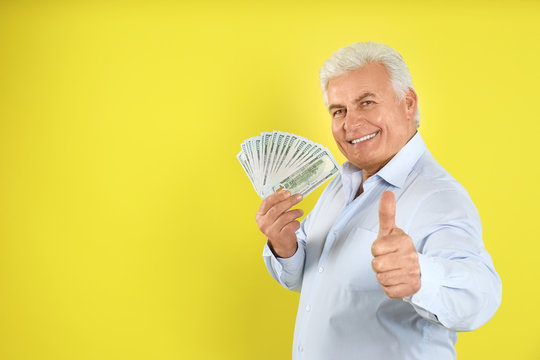 Happy senior man with cash money on yellow background. Space for text