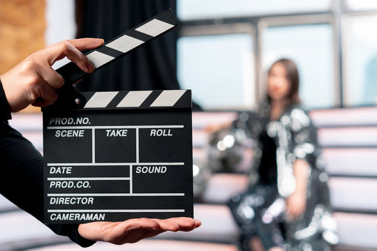 Focus On Clapper Board With Woman On Stage On Background. Movie Or Clip Production Backstage