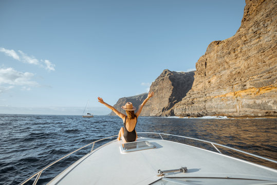 Woman enjoying ocean voyage sitting back on the yacht nose while sailing near the breathtaking rocky coast on a sunset
