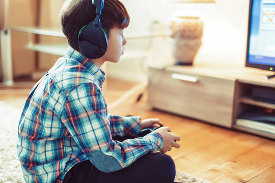 Little boy playing video game by controller side view