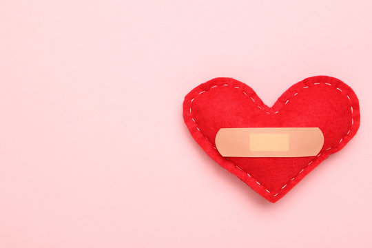 Red fabric heart with bandage on pink background