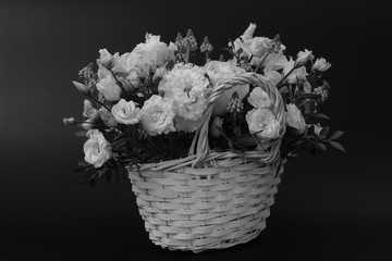 Foto op Canvas Lelie Bouquet. Composition of fresh, delicate flowers in a white basket against a dark background. Black and white photo.