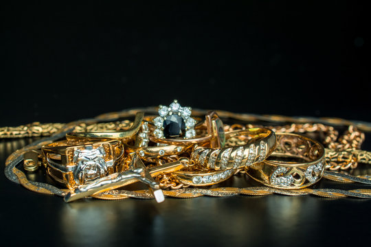 Gold jewelry rings chain, earrings   on   dark background.