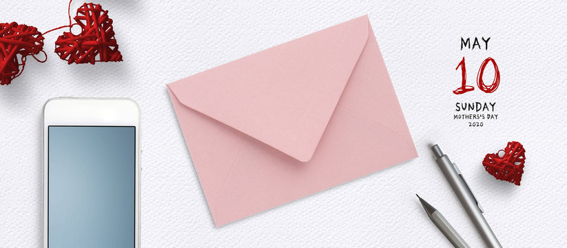 envelope and smartphone on paper background with reminder for mother's day 2020
