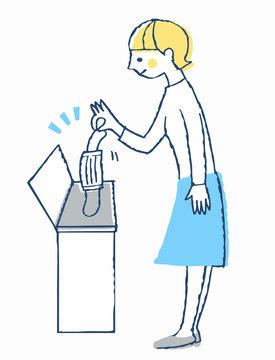 使用済みマスクをゴミ箱に入れる女性