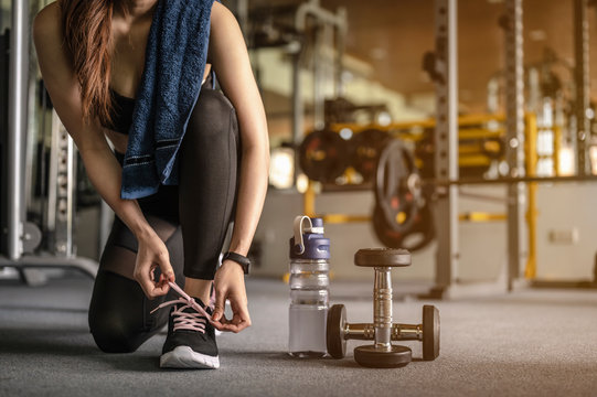 Women are using their hands to tie their shoes, have a dumbbell and a bottle of water. Prepare for exercise in the gym at sunset. fitness, workout, gym exercise, lifestyle and healthy concept.
