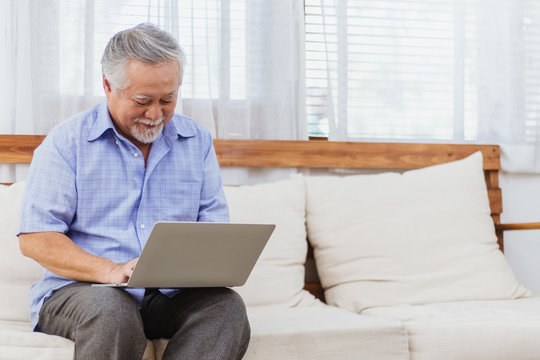 Happy healthy Asian senior elderly man working on computer at home. Retired grandfather enjoy learning or studying online course or e-learning via webinar by using laptop. Elder activity and lifestyle