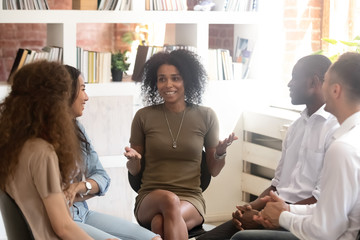 Smiling African American psychologist coach speaking with diverse people