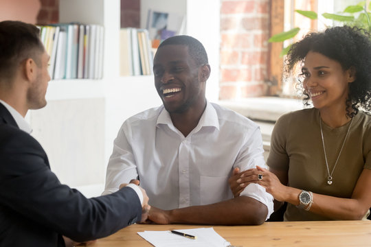 Happy African American couple handshaking manager, realtor, making deal