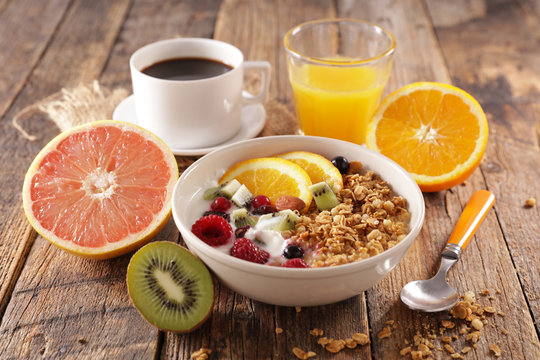 healthy breakfast with muesli and fruit, coffee cup and orange juice