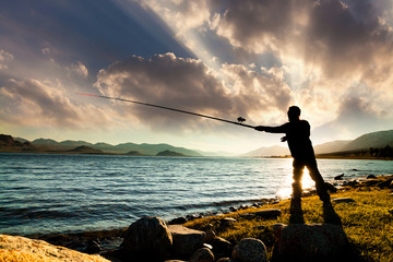 Poster Peche Silhouette of a fisherman at sunset on a lake. Summer vacation on the lake