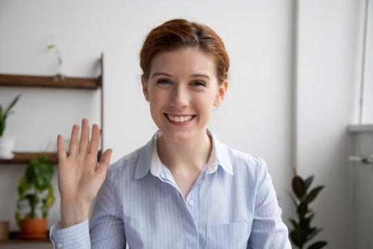 Head shot portrait of attractive smiling businesswoman waving hand