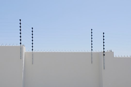 long upright poles holding electric fencing cable on a boundary wall