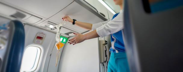 Aeroflot shows how to use an oxygen mask on board, Air hostess demonstrate safety procedures to passengers prior before airplane flight take-off,banner for website