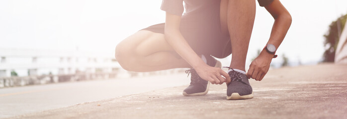 Tie a shoe,Asian male jogger athlete training and doing workout outdoors on a street, He tying laces for jogging on road with running shoes. Runner getting ready for exercise. Sport lifestyle concept Fotomurales