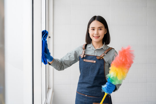 Maid Cleaning Service Concept,Beautiful asian maid women smiling and holding microfiber and cleaner spray for cleaning service feeling happiness  confident ,copy space in room