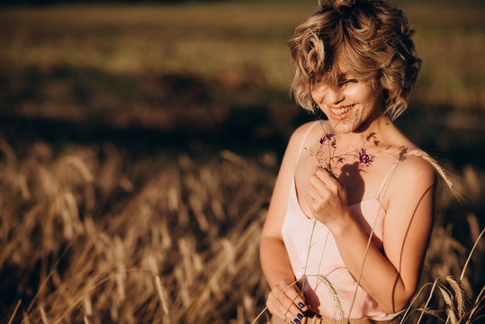 Freedom a happy and beautiful woman with curly hair enjoys the summer sun in a field with wheat on a sunny day. Open space.