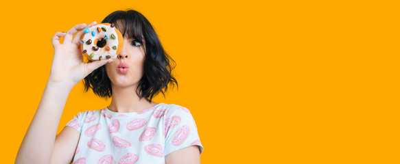 Charming brunette girl looking through a donut is feeling amazed posing on a yellow background with freespace Wall mural