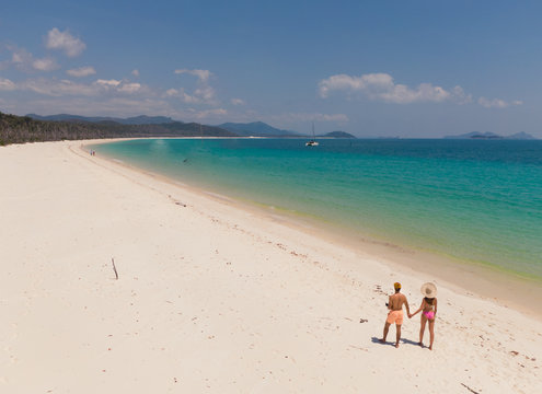 Couple on honeymoon on beach. Whitsundays aerial view, with turquoise ocean, white sand. Dramatic DRONE view from above. Travel, holiday, vacation, paradise. Shot in Whitsundays Islands, Queenstown, A