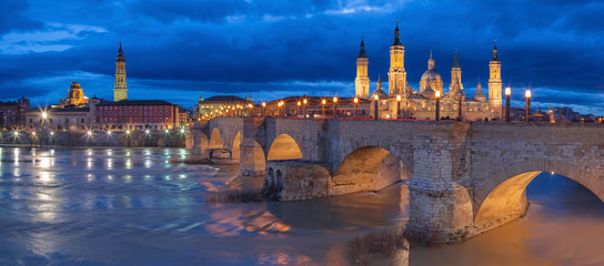 Wall Mural - Zaragoza - The panorama with the bridge Puente de Piedra and Basilica del Pilar at dusk.
