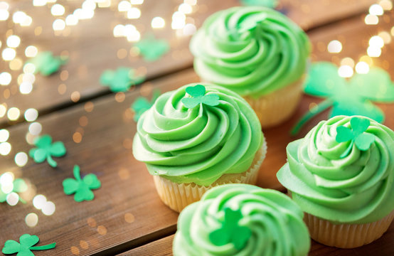 st patricks day, food and holidays concept - close up of green cupcakes and shamrock on wooden table over festive lights