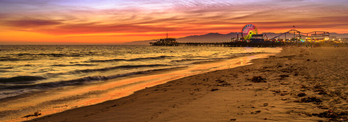 Santa Monica Historic Landmark, California, United States. Amazing landscape of iconic Santa Monica Pier at orange red sunset sky from beach on Paficif Ocean. Banner panorama background.