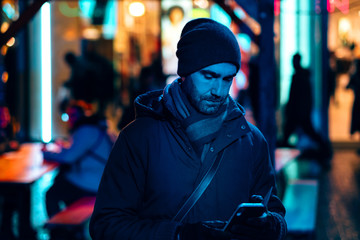 man outdoor at night in the city using a mobile phone surrounded by the neon sign lights