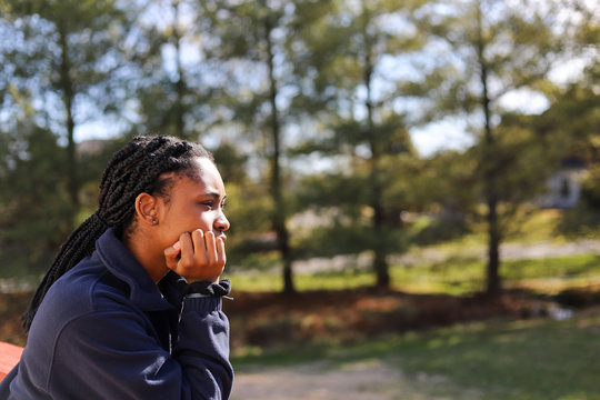 portrait of an African-American teenaged girl looking away in deep thought and feeling sad and lonely